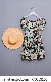 female floral clothes with straw hat on hanging-gray background