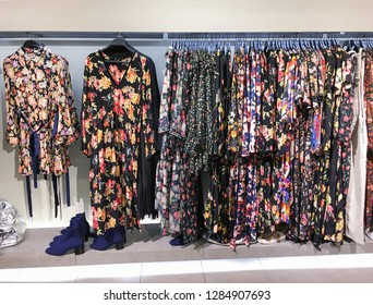 Female floral clothes ,sundress ,high hell ,boots hanging a row-in store  '