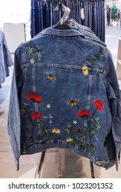 Female floral jeans jacket, clothes hanging in a row-in stores