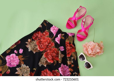 female, floral long skirt with red shoes,sunglasses –light green background