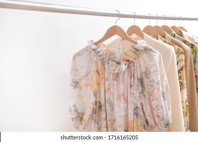 female floral ,palm pattern summer sundress and three business suit formal jacket and jacket and floral ,palm pattern summer shirts , shirt blouse isolated and on hanger