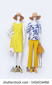 Female in floral pattern clothing with sundress and yellow trousers ,straw hat, handbag on two mannequin isolated