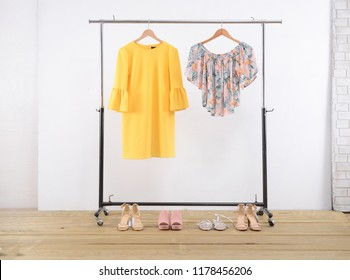 female , floral shirts clothes and sundress on hanger with different shoes –wooden background