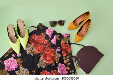 Female floral skirt ,sunglasses, shoes and light green background