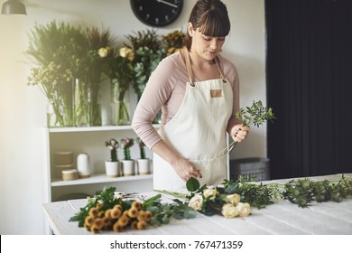 Female florist arranging a bouquet of mixed flowers while working at a table in her flower shop