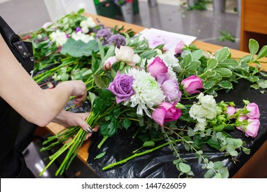 Female florist create a bouquet at workplace. Floristics workshop. Making beautiful flower bouquets and floral decorations.