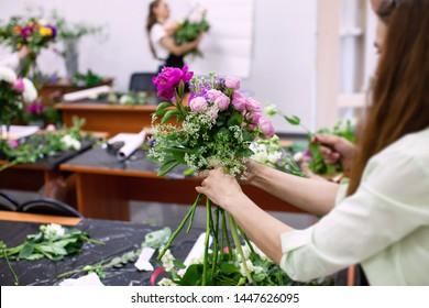 Female florist create a bouquet at workplace. Floristics workshop. Making beautiful flower bouquets and floral decorations.