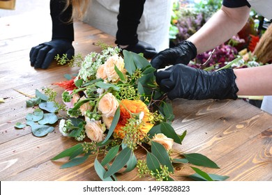 Female florist create a bouquet at workplace. Floristics workshop. Flowers delivery, creating order. Family flower's business. Lifestyle flower shop.