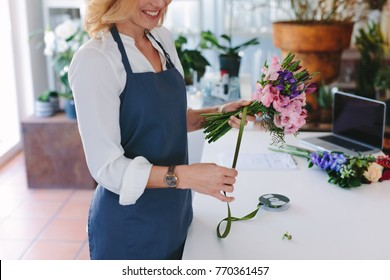 Female florist creating bouquet of flowers at shop. Woman florist tying flowers with ribbon and designing bouquet on counter.