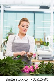 Female florist cutting stem on rose at counter in flower shop