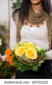 Female florist in flower shop or nursery presenting her plants on display
