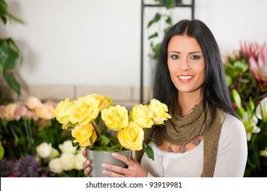 Female florist in flower shop or nursery presenting yellow roses