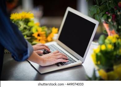 Female florist hand using laptop in flower shop