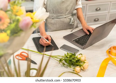Female florist receiving an order on laptop, making notes in notebook. Woman works in his own flower shop.