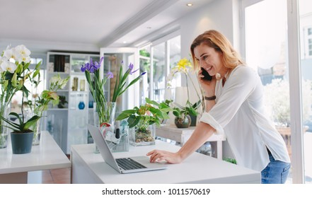 Female florist standing at her flower shop counter using mobile phone and laptop to take orders for her store. Woman flower shop owner taking online orders.