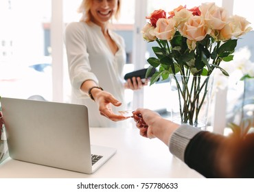 Female florist taking credit card for payment from customer. Client paying for flowers with debit card. Cashless payments at flower shop. Focus on hands.