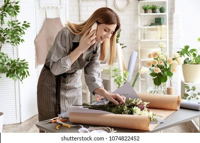 Female florist talking on phone while making bouquet at workplace