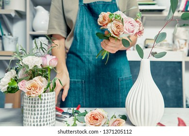 Female florist unfocused in flower shop making beautiful artificial bouquet. A teacher of floristry in master classes or courses. Professional, floral, decoration studio. Copy space for design