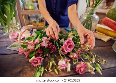 Female florist working with flowers in workshop