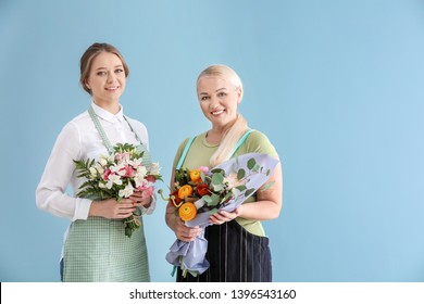 Female florists with bouquets on color background