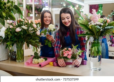 Female florists are creating bouquets. One woman collecting white roses for a bunch, another is tying a box with violet ribbon. Working in local flower shop.