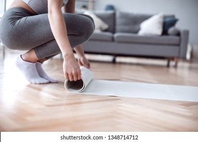 Female folding rubber carpet after yoga session finished sport training. Wellness and active healthy lifestyle concept. Woman yoga mat at home.