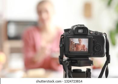 Female food blogger recording video indoors