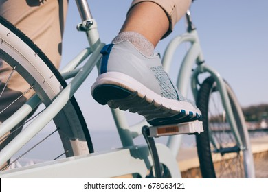 Female foot in a blue sneaker and a bicycle on the beach close-up