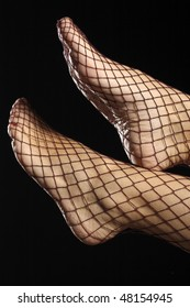 Female foot in fishnet stockings