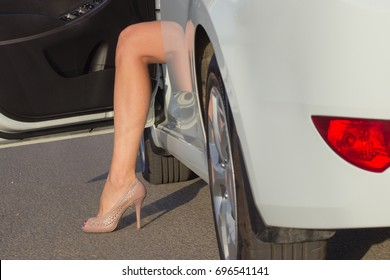 Female foot in heels at the door of the car.