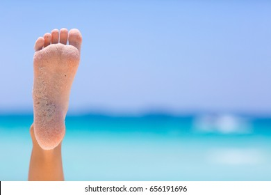 Female foot on blue sky and sea background