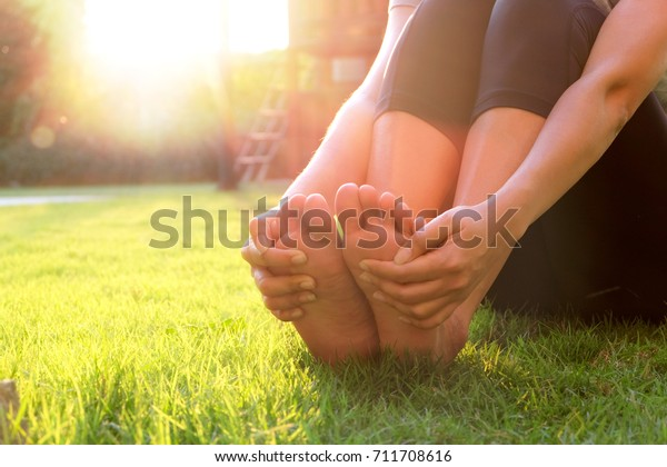 Female foot pain sitting on the grass, massage and stretch her foot muscles, sunset at the park, health concepts, yoga and relaxation exercises.