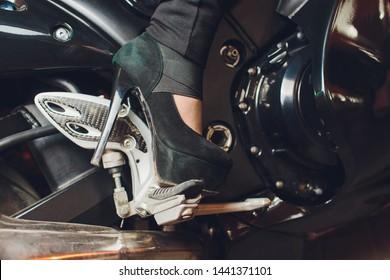 Female foot in slippers on a motorcycle kickstart.