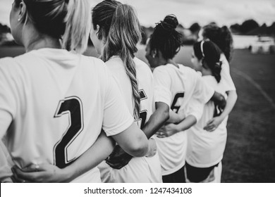 Female football players huddling together