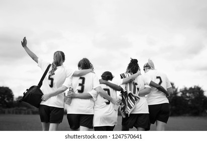 Female football players huddling and walking together