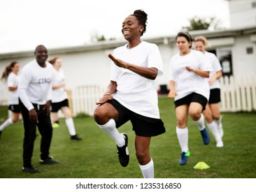 Female football players warming up on the field