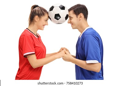 Female footballer and a male footballer holding a football between their heads isolated on white background