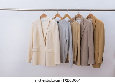 female, formal business four colour suit, jacket and sweater on hanger