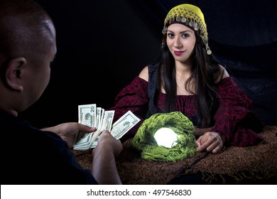 Female fortune teller or con artist swindling money from a male customer via fraud.  The man is a gullible victim and the psychic is a fraudulent liar swindling for cash.