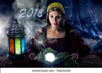 Female fortune teller doing a psychic reading with a cystal ball predicting fate or destiny and the future of the year 2018
