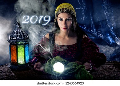 Female fortune teller or psychic reading with a cystal ball predicting the future of the New Year 2019