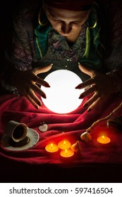 Female fortuneteller with her hands above lighted crystal ball