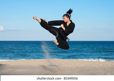 A female, fourth degree, Taekwondo black belt athlete performs a midair jumping kick on the beach.