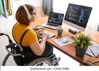 Female freelance programmer in modern headphones sitting in wheelchair and using computers while coding web game at home