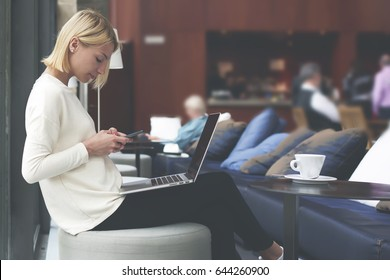 Female freelancer connecting to wireless via smartphone while having a coffee in modern cafe interior, modern business woman working on her net-book sitting at library or loft studio with big windows