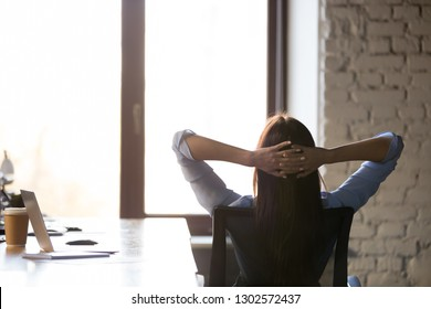 Female freelancer or employee lean back in chair relaxing or taking break from work, calm woman stretch hands over head look in window, dreaming or visualizing, worker have break resting