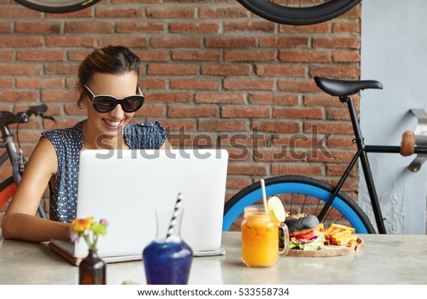 Female freelancer with happy smile working remotely on laptop. Successful food blogger typing new post on her blog, sitting at table with burger and fresh orange juice against red brick wall at cafe