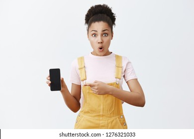 Female friend showing girlfriend strange message she received, holding smartphone and pointing at screen with index finger, folding lips from interest and surprise, standing shocked and impressed