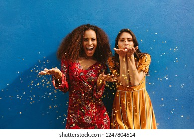 Female friends blowing off magic glitter. Excited women having fun against blue wall.