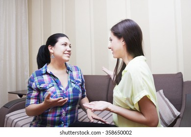 Female friends to chat at home on a sofa